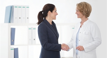 Homecare, smiling female physician/prescriber in physician's officel talking to female sales rep, shake hands