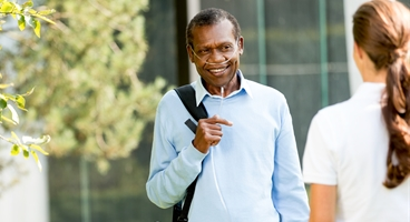 Smiling oxygen patient with nasal cannula and mobile concentrator walking in a park.